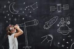 Schoolmeisje die door een telescoop kijken stock afbeeldingen