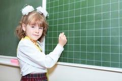 Schoolmeisje die door krijt op groen bord schrijven Stock Afbeeldingen
