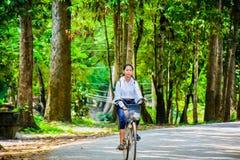 Schoolmeisje die een fiets berijden aan school, Kambodja stock foto's