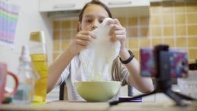 Schoolmeisje die en eigengemaakt pluizig slijm op de keuken uitrekken drukken stock videobeelden