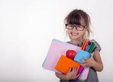 Schoolmeisje die in oogglazen vele schoollevering houden: pennen, notitieboekjes, schaar en appel stock afbeelding