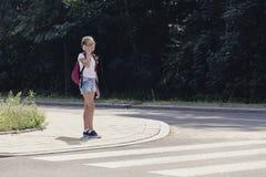 Schoolmeisje die op de telefoon spreken en in voetgangersoversteekplaats lopen stock afbeeldingen