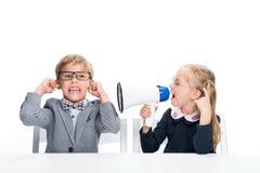 Schoolmeisje die op jongen met luidspreker schreeuwen royalty-vrije stock foto's