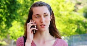 Schoolmeisje die op mobiele telefoon spreken stock footage