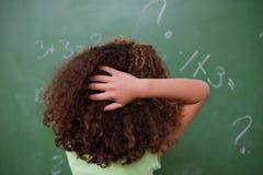 Schoolmeisje die over algebra denken terwijl het krassen van de rug van h royalty-vrije stock afbeelding