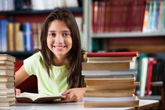 Schoolmeisje die terwijl het Zitten met Stapel van glimlachen stock foto