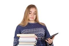 Schoolmeisje die tussen boeken en een ebooklezer proberen te beslissen Royalty-vrije Stock Foto's