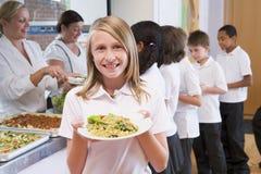 Schoolmeisje in een schoolcafetaria Stock Afbeeldingen
