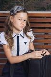 Schoolmeisje in eenvormig wachten voor de bus aan school Stock Foto's