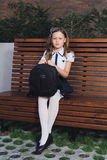 Schoolmeisje in eenvormig wachten voor de bus aan school Stock Afbeeldingen