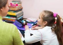 Schoolmeisje en moeder die thuiswerk doen Stock Afbeeldingen