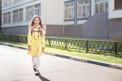 Schoolmeisje in gele laag Royalty-vrije Stock Foto's
