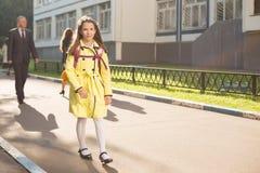Schoolmeisje in gele laag Stock Foto