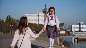 Schoolmeisje loopt met haar moeder, steadicam, vooraanzicht op zee-oevers stock videobeelden