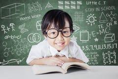 Schoolmeisje met gekrabbelachtergrond op het bord Stock Foto's