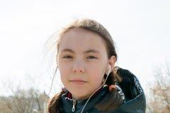 Schoolmeisje met rugzak in warm zonnig weer op de straat met hoofdtelefoons die aan muziek in het gadget luisteren royalty-vrije stock foto's