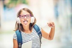 Schoolmeisje met zak, rugzak Portret van het moderne gelukkige meisje van de tienerschool met de hoofdtelefoons en de tablet van  Royalty-vrije Stock Foto's