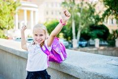 Schoolmeisje in school eenvormige tonende handen omhoog Stock Afbeeldingen