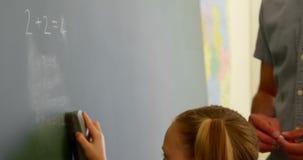 Schoolmeisje schoonmakend bord met een stofdoek in een klaslokaal op school 4k stock footage