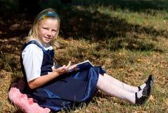 Schoolmeisje in tuin royalty-vrije stock afbeelding