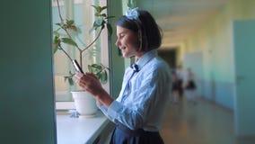 Schoolmeisjeonderwijs met smartphones bij schoolconcept Jonge meisjestiener en het gebruiken van smartphone die door het venster  stock video