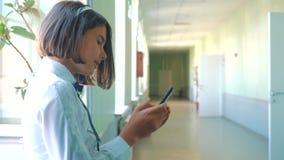 Schoolmeisjeonderwijs met smartphones bij schoolconcept Jonge meisjestiener en het gebruiken van smartphone die door het venster  stock videobeelden