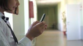 Schoolmeisjeonderwijs met smartphones bij schoolconcept Jonge meisjestiener en het gebruiken van smartphone die zich door levenss stock videobeelden