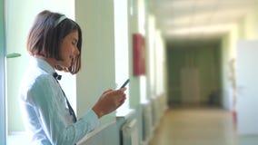 Schoolmeisjeonderwijs met smartphones bij schoolconcept Jonge meisjestiener en het gebruiken van smartphonelevensstijl die zich d stock footage