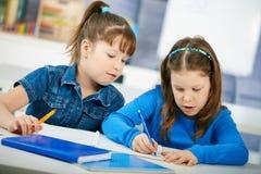 Schoolmeisjes die in klaslokaal leren Stock Fotografie