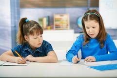 Schoolmeisjes die in klaslokaal leren Stock Foto