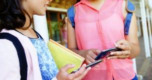Schoolmeisjes die mobiele telefoon met behulp van stock video