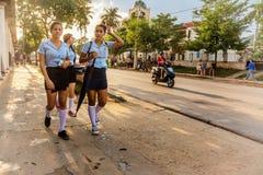 Schoolmeisjes in eenvormige gang de straten van Vinales royalty-vrije stock fotografie