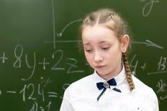 Schoolmeisjetiener droevig bij het schoolbord stock afbeelding