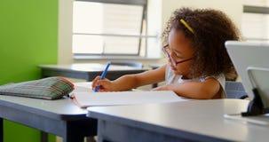 Schoolmeisjezitting bij bureau en het bestuderen in klaslokaal 4k stock videobeelden