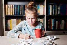 Schoolmeisjezitting bij lijst met in hand potlood royalty-vrije stock afbeeldingen