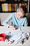 Schoolmeisjezitting bij lijst met in hand potlood Stock Fotografie