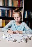 Schoolmeisjezitting bij lijst met in hand potlood royalty-vrije stock foto's