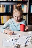 Schoolmeisjezitting bij lijst met in hand potlood stock foto