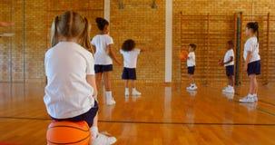 Schoolmeisjezitting op basketbal in basketbalhof op school 4k stock videobeelden
