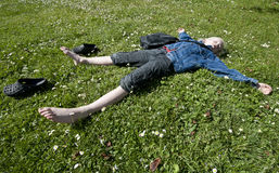 Schools out. Young blond boy taking a breather on a lawn full of with flower Stock Photo