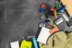 Schooltas en veelvoudige kantoorbehoeftenpunten op bord stock foto's