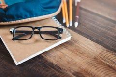 Schooltas, notitieboekje, potlood, pen en oogglazen op een houten lijst Selectieve nadruk  stock fotografie