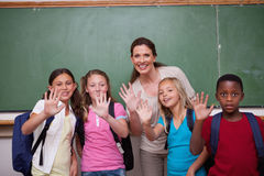 Schoolteacher and her pupils waving at the camera Stock Photos