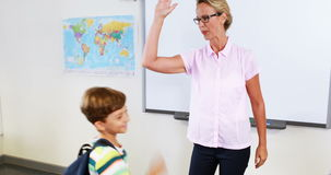 Schoolteacher and kids giving high five in classroom