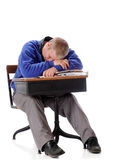 Schooltime Snooze. A mature man in an old school desk falling asleep on his pile of papers and books.  On a white background Stock Photos