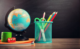 Schooltoebehoren op de lijst met bordachtergrond Stock Foto