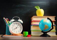 Schooltoebehoren op de lijst met bordachtergrond Stock Foto's