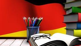 Schooltoebehoren op een lijst met het Duitse vlag drijven stock video