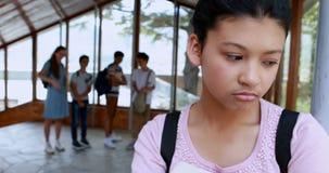 Schoolvrienden die een droevig meisje in gang intimideren stock video