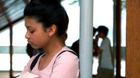 Schoolvrienden die een droevig meisje in gang intimideren